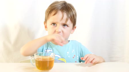 pushed : The child refuses to drink tea. The boy is not satisfied with the food. The child pushed his glass with his hand. Stock Footage