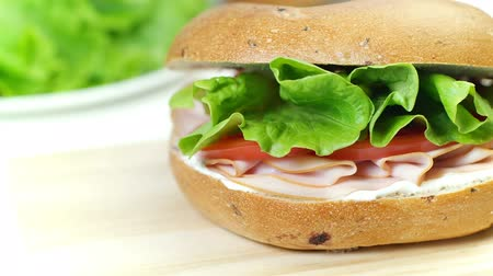 pronto a comer : Bagel sandwich with cream cheese, sausage, tomato and lettuce leaf, closeup, dolly shot