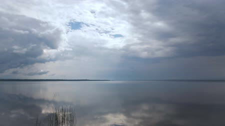 Time-lapse of clouds flying over calm lake, wide angle shot