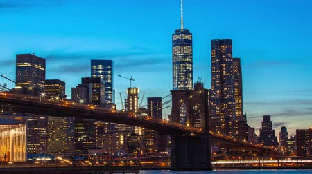 večer : Time lapse sunset shot of lower Manhattan and Brooklyn bridge, New York, USA
