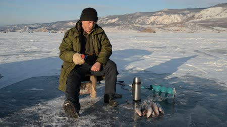 szczupak : Fisherman is a man in winter fishing. A real fisherman is sitting and fishing. Sometimes pulls ice from the hole to prevent it from freezing. Nearby is a fish caught omul and grayling, another flask and a hand icebreaker.