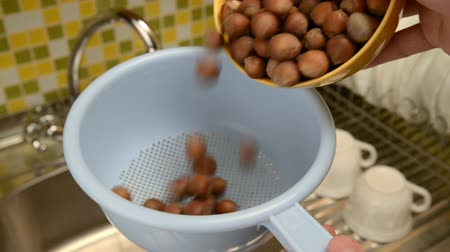 lave : Nut hazelnut. Wash the nuts in the colander in the kitchen in the sink. Under the stool of water, wash nuts with hands from dirt.