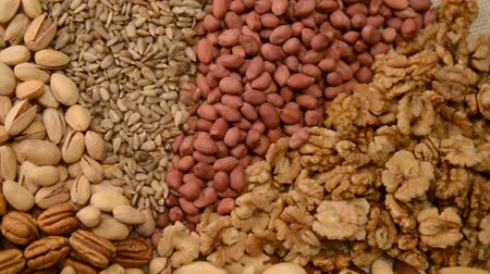 top ten : Nuts mix in a canvas bag in table. Ten kinds of nuts: pecan, brazil, cedar, sunflower, hazelnut, almond, peanut, walnut, pistachio, cashew. The nut mix rotates on the turntable