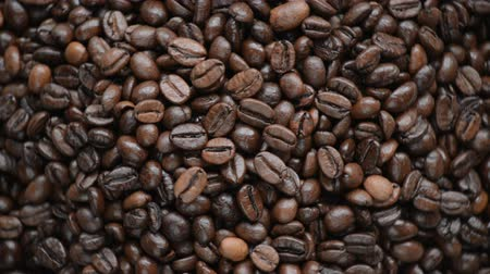 xícara de café : Coffee beans turn on the turntable. The subject background is spinning and moving. The camera is static. On the table is a linen cloth bag.