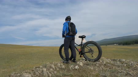 etli : Fat bike also called fatbike or fat-tire bike in summer driving through the hills. The guy is riding a bike along the sand and grass high in the mountains. He performs some tricks and runs dangerously. In the distance, rocks and the sea can be seen. Stok Video