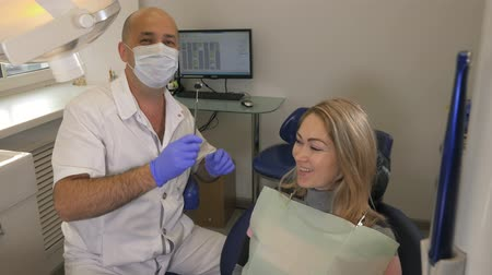 zubní lékařství : Professional look. Professional male dentist orthodontist checking teeth of his female client. The doctor shows the woman an album with photos of teeth, with examples of works.