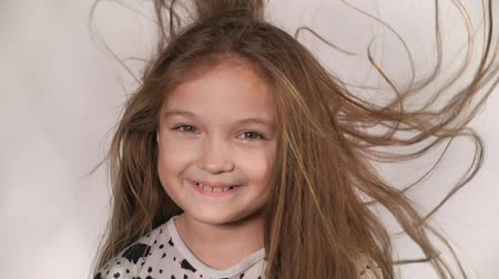 ventoso : Happy little girl in the studio on a gray background. She jumps, shows different emotions. Hair fluttering from the wind. Super slow motion, shot at 180fps.