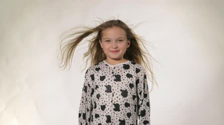 ветер : Happy little girl in the studio on a gray background. She jumps, shows different emotions. Hair fluttering from the wind. Super slow motion, shot at 60fps. Стоковые видеозаписи