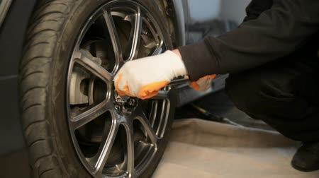 kavramak : Auto mechanic working on brakes in a car repair shop domestic garage. Professional repair of a car. Stok Video