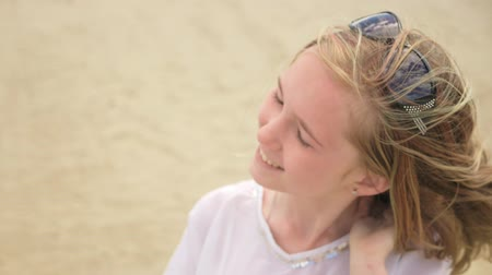 hlazení : Close up portrait of beautiful young woman teenager. Hair blowing in wind on beach in slow motion. She is smiling and attractive. On her head are sunglasses. Dostupné videozáznamy
