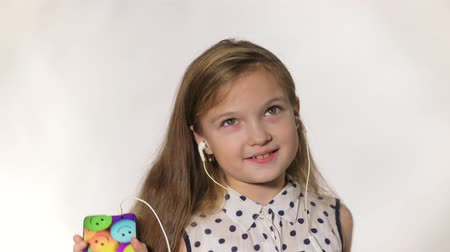 risonho : Child with earflaps dancing at studio background. The girl listens to music on the smartphone. The kid has loose long hair. Shooted on a gray white background.