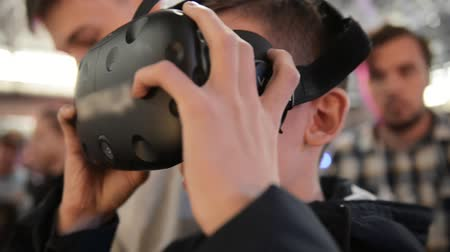 personal computers : The guy plays in the VR headset virtual reality at a meeting events of computer game fans. In the background there are a lot of people in the blur, bright and lights from concert. Stock Footage
