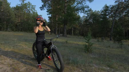 tvrdé dřevo : Fat bike also called fatbike or fat-tire bike in summer riding in the forest. Beautiful girl and her bicycle in the forest. She enters the frame and takes off her helmet and glasses.