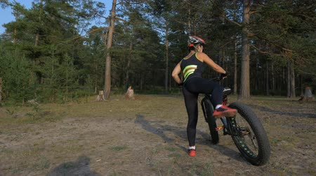 kaseta : Fat bike also called fatbike or fat-tire bike in summer riding in the forest. Beautiful girl and her bicycle in the forest. She is posing near her bicycle. Then she leaves. Wideo