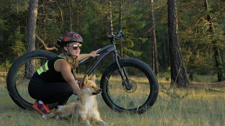 etli : Fat bike also called fatbike or fat-tire bike in summer riding in the forest. Beautiful girl and her bicycle in the forest. She met the dog in the woods and stroked her. The dog is very kind and good.