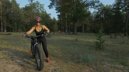 kaseta : Fat bike also called fatbike or fat-tire bike in summer riding in the forest. Beautiful girl and her bicycle in the forest. She puts her bike more comfortable to roll down beautifully.
