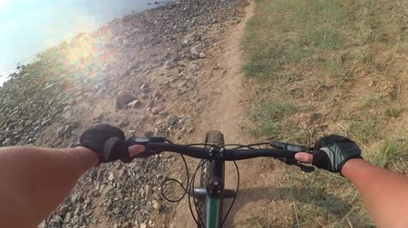 pace : Fat bike also called fatbike or fat-tire bike in summer riding. Driving on different surfaces of stones, sand, grass, mud. A view from the first person to the steering wheel, hands and road. Stock Footage