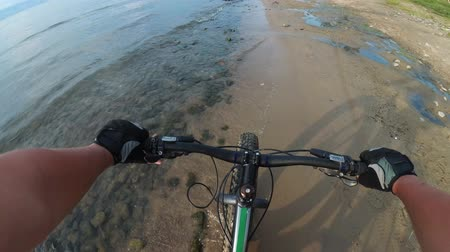greater : Fat bike also called fatbike or fat-tire bike in summer riding. Driving on different surfaces of stones, sand, grass, mud. A view from the first person to the steering wheel, hands and road. Stock Footage
