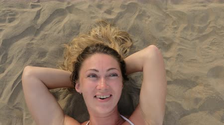 enticing : The woman lies directly on the sandy beach. He looks at the camera, smiles, laughs. Shes mysterious and seductive. View from above.