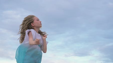 friendship dance : Two children dance and indulge on the beach. Children perform dancing stunts tricks. Hair fluttering in the wind. The kid spin and jump, shake their heads. One girl is a teenager. Stock Footage