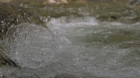 sıçramasına : Beautiful water in a mountain river in slow motion video. Shooting speed 180fps, slow motion. Live shooting of the most beautiful nature river mountain water. The camera is static.