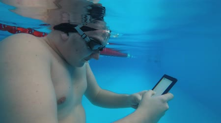 ebook : The guy is reading an electronic book underwater. This is a special waterproof electronic device. You can read the text and show signs directly underwater. Stock Footage