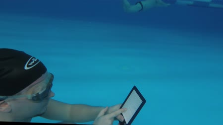 ebook : Man reads an electronic book underwater. This is a special waterproof electronic device. You can read the text and show signs directly underwater.