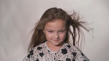 gently : Happy little girl in the studio on a gray background. She jumps, shows different emotions. Hair fluttering from the wind. Super slow motion, shot at 180fps.