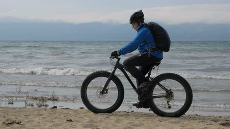 him : Fat bike also called fatbike or fat-tire bike in summer driving on the beach. The guy was riding a bicycle, then stopped and sat on the wheel of his bicycle. He looks at the sea and enjoys his sight.