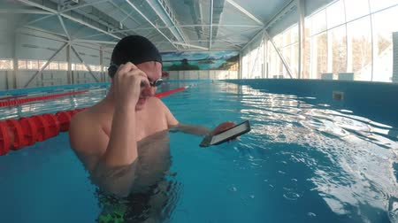 e book : The guy is reading an electronic book underwater. This is a special waterproof electronic device. You can read the text and show signs directly underwater. Stock Footage