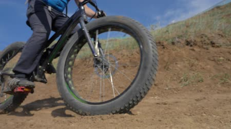 him : Fat bike also called fatbike or fat-tire bike in summer driving on the road. The guy rides by the hill on a sand clay path. The bicycle is allowed into the drift. Slow motion shooting 180fps. Stock Footage