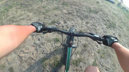 гелий : Fat bike also called fatbike or fat-tire bike in summer riding. Driving on different surfaces of stones, sand, grass, mud. A view from the first person to the steering wheel, hands and road. Стоковые видеозаписи