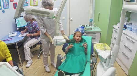 affect : Child with a mother at a dentists reception. The girl lies in the chair, behind her mother. The doctor works with an assistant. Procedure for drilling a tooth. Setting a temporary seal. Using the x-ray machine. Stock Footage