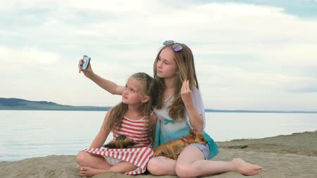 telephone handset : Two teenage children are sitting on the beach. They wear sunglasses. Sisters communicate with each other and do selfie on the phone. Trying to upload your photo to the Internet. Stock Footage