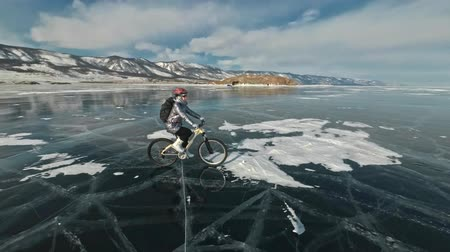 zíper : Woman is riding bicycle on the ice. The girl is dressed in a silvery down jacket, cycling backpack and helmet. Ice of the frozen Lake Baikal. The tires on the bicycle are covered with special spikes. The traveler is ride a cycle.
