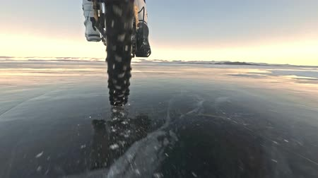 ağarmış : View of the tire. Shooting 60fps actioncam. Woman is riding bicycle on the ice. Ice of the frozen Lake Baikal. The tires on the bicycle are covered with special spikes. The traveler is ride a cycle. Stok Video