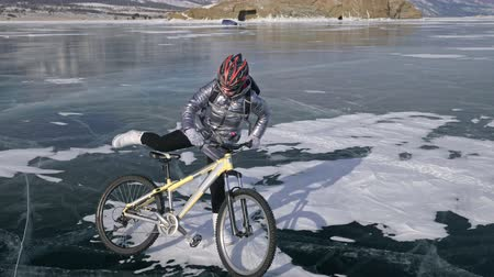 rampouch : Woman is walking beside bicycle on the ice. The girl is dressed in a silvery down jacket, backpack and helmet. Ice of the frozen Lake Baikal. The tires on the bicycle are covered with special spikes. The traveler is ride a cycle. Dostupné videozáznamy