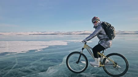 kopec : Woman is riding bicycle on the ice. The girl is dressed in a silvery down jacket, cycling backpack and helmet. Ice of the frozen Lake Baikal. The tires on the bicycle are covered with special spikes. The traveler is ride a cycle.