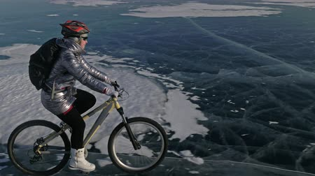 enduro : Woman is riding bicycle on the ice. The girl is dressed in a silvery down jacket, cycling backpack and helmet. Shooting with a quadrocopter drone. Ice of the frozen Lake Baikal. The tires on the bicycle are covered with special spikes.
