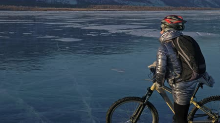 frozen lake : Woman is riding bicycle on the ice. The girl is dressed in a silvery down jacket, cycling backpack and helmet. The cyclist rides and stops to rest. He sits down on the wheel and partially takes off his gear. The traveler is ride a cycle.