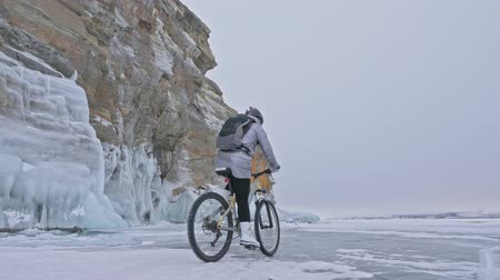 шлем : Woman is riding bicycle near the ice grotto. The rock with ice caves and icicles is very beautiful. The girl is dressed in silvery down jacket, cycling backpack and helmet. The tires on covered with special spikes. The traveler is ride cycle.