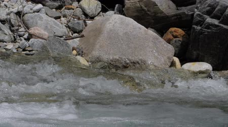sıçramasına : Beautiful water in a mountain river in slow motion video. Shooting speed 180fps, slow motion. Live shooting of the most beautiful nature river mountain water. The camera is not static. Water 1 part 2. Stok Video