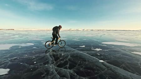 aro : Man is riding a bicycle on ice. The cyclist is dressed in a gray down jacket, backpack and helmet. Ice of the frozen Lake Baikal. The tires on the bicycle are covered with special spikes. The traveler is ride a cycle.