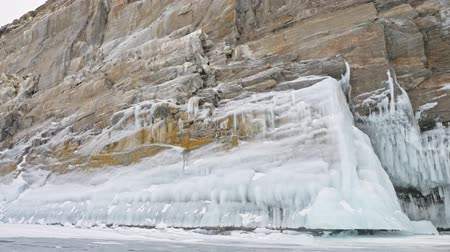 застежка : Man is riding bicycle near the ice grotto. The rock with ice caves and icicles is very beautiful. The cyclist is dressed in gray down jacket, cycling backpack and helmet. The tires on covered with special spikes. The traveler is ride cycle.