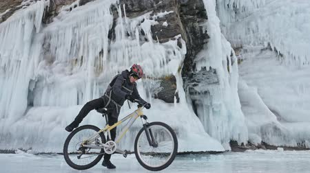 с шипами : Man is walking beside bicycle near the ice grotto. The rock with ice caves and icicles is very beautiful. The cyclist is dressed in gray down jacket, cycling backpack and helmet. The tires on covered with special spikes. The traveler is ride cycle.