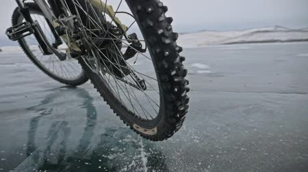 sağlam : View of tire. Shooting 180fps. Man is riding bicycle on the ice. The cyclist cuts in front of the camera. Pieces of ice fly in us. Ice of the frozen Lake Baikal. The tires on the bicycle are covered with special spikes. The traveler is ride a cycle.