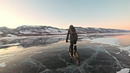 water rail : Man is riding a bicycle on ice. The cyclist is dressed in a gray down jacket, backpack and helmet. Ice of the frozen Lake Baikal. The tires on the bicycle are covered with special spikes. The traveler is ride a cycle.
