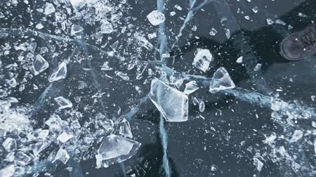 camera rotation : Man in the mittens smashes the ice on the ice. Slow motion. The camera moves behind the ice. A piece of ice is very beautifully broken about the icy with magical cracks. In the frame, a lot of particles of frozen water.