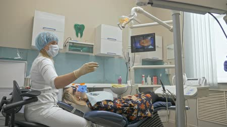 ambulância : Doctor used special Dental Intraoral Check Digital Micro Camera to exam teeth. On the monitor dentist and patient see video of teeth, tooth problems. Orthodontist used microscope. Dentist is treating patient in modern dental office.