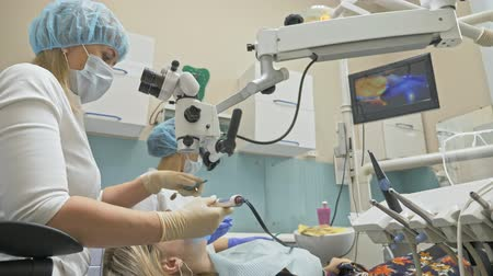 salya : Doctor used special Dental Intraoral Check Digital Micro Camera to exam teeth. On the monitor dentist and patient see video of teeth, tooth problems. Orthodontist used microscope. Dentist is treating patient in modern dental office.